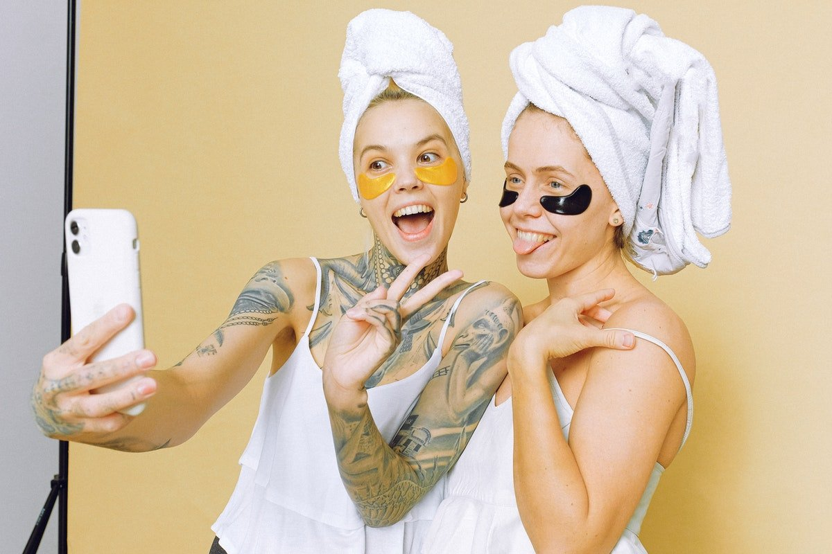 Two women in bathrobes enjoying a spa day for Sisters Day