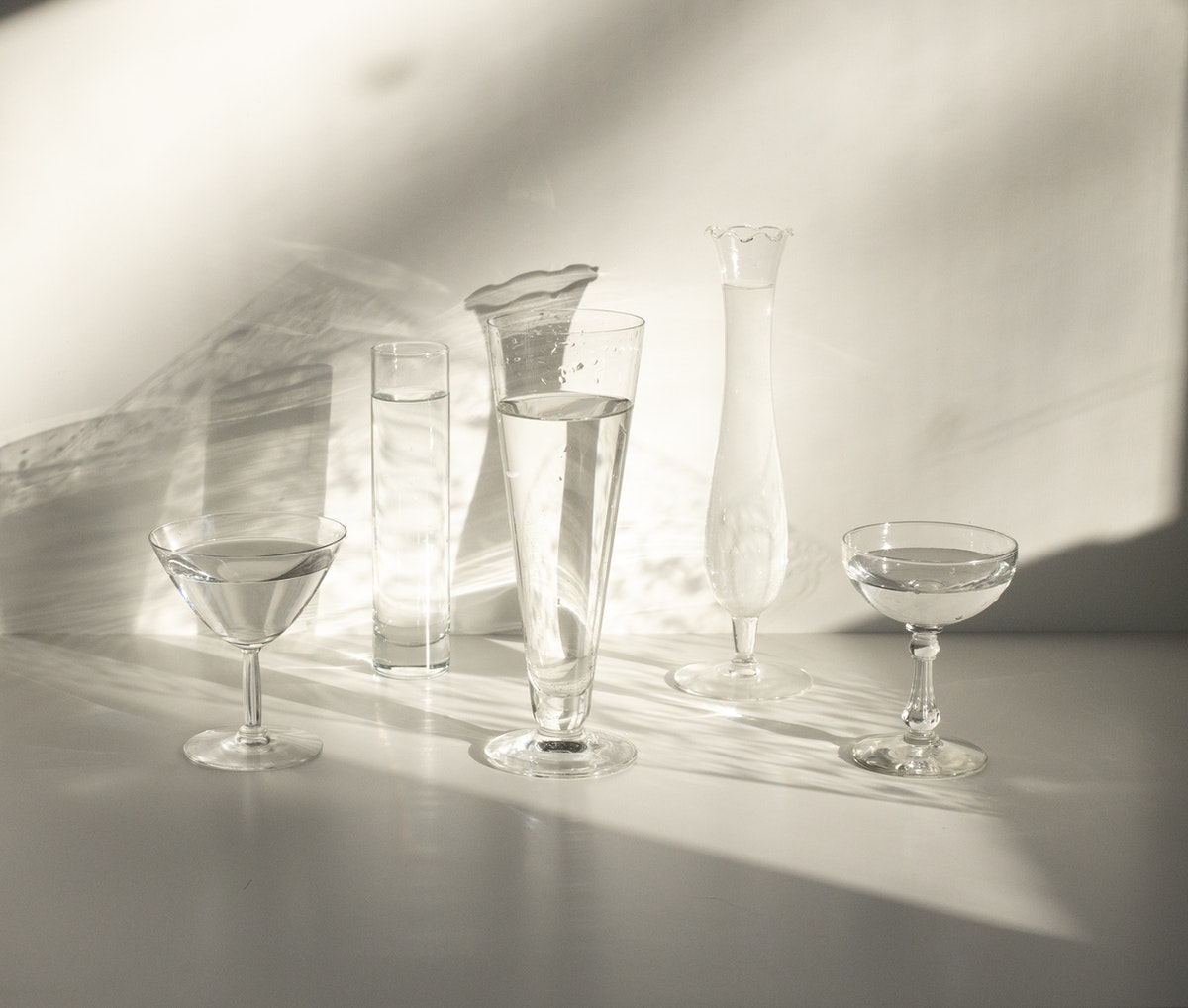 Crystal glasses lined up against a white wall with shadows against the wall. Crystal vases and glasses like this are perfect gifts for a crystal wedding anniversary.