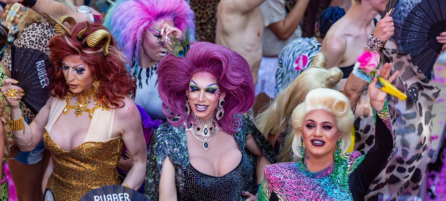 A crowd of drag queens smiling, dressed in bright colours