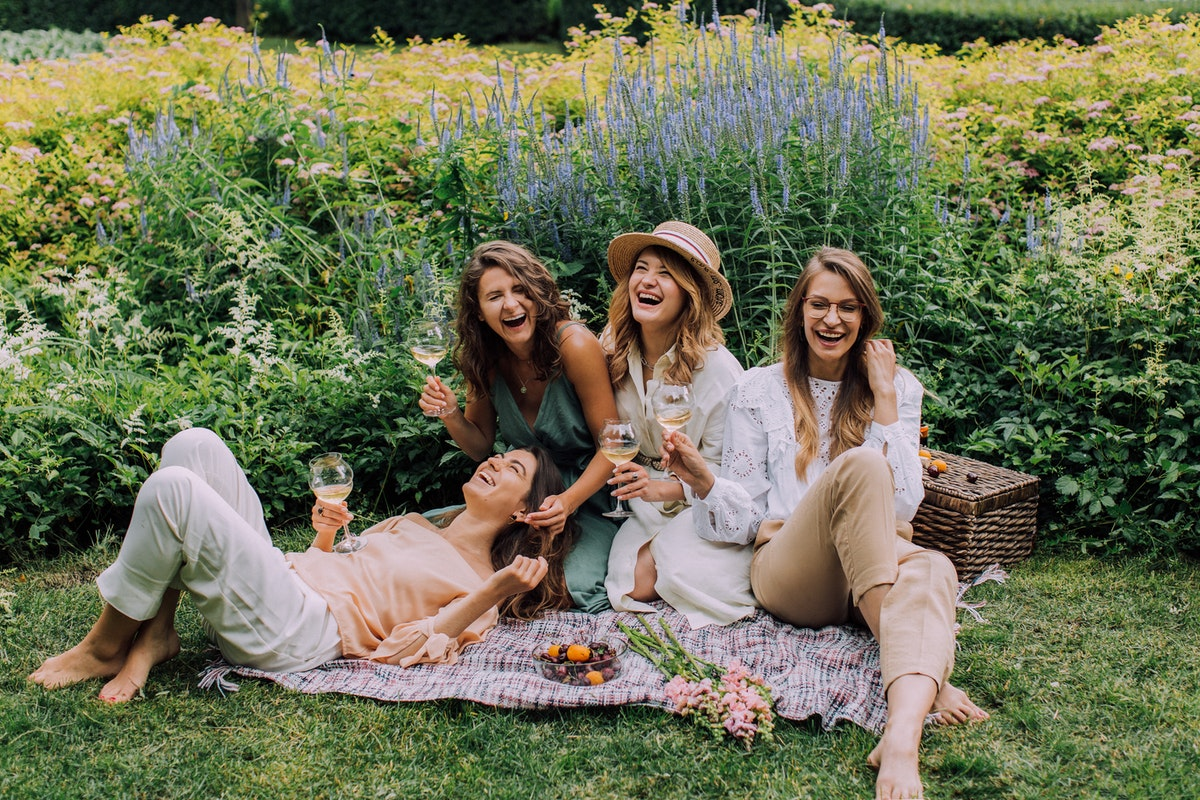 A group of women having a picnic and laughing. Spa weekends make great hen party ideas