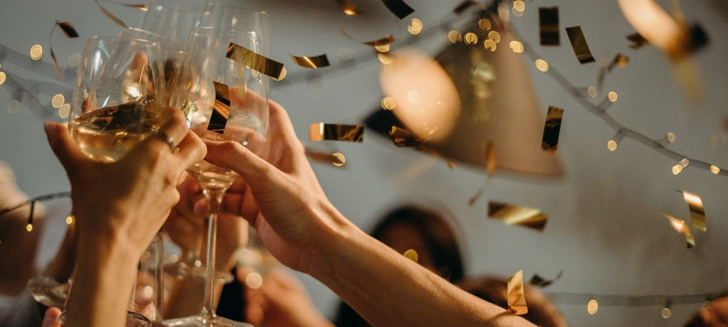 Hands clinking champagne glasses at a hen party