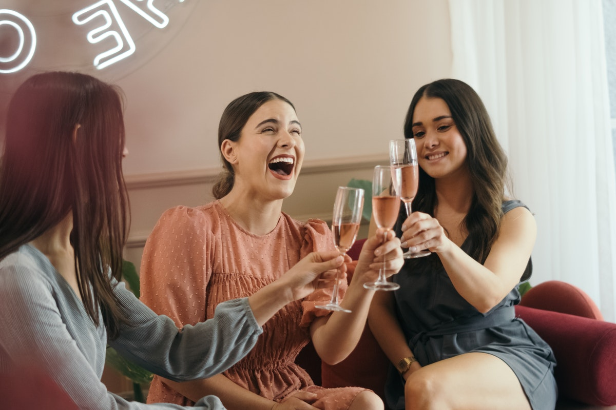 Three women toasting with champagne glasses at a hen party