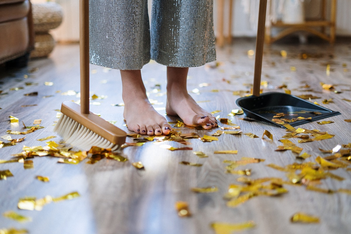 A person sweeping up gold confetti after a housewarming party