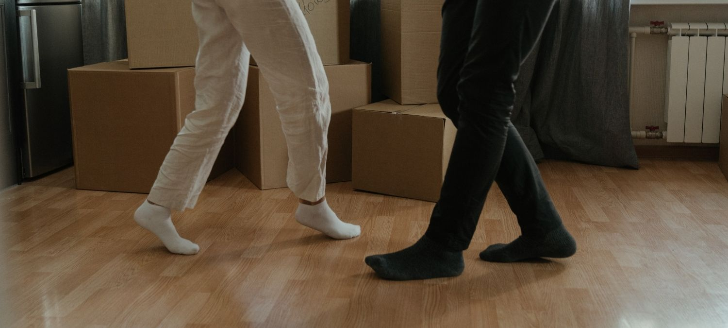 Two people dancing in a new home with moving boxes