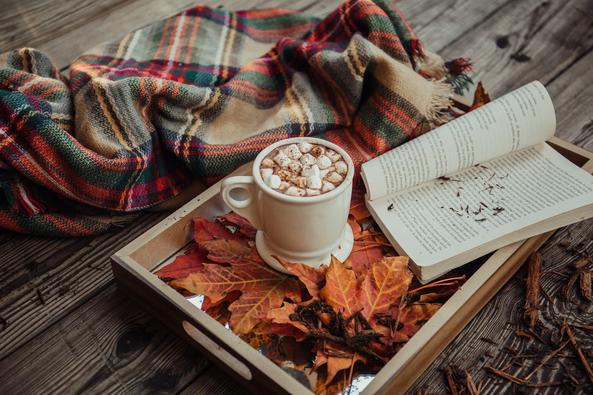 A wooden tray with a mug of hot chocolate, open book and autumn leaves