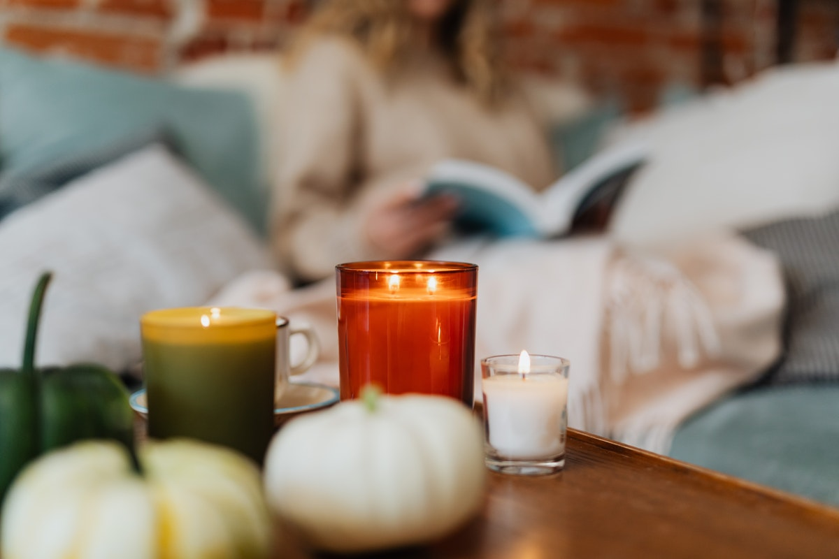 A focused photo of autumnal candles and pumpkins. A person is reading a book in the background.