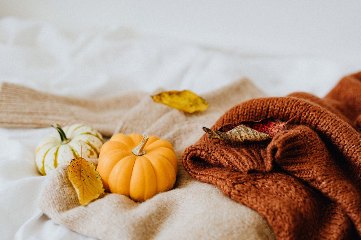 A pumpkin sat on a pile of wool blankets on a bed. Pumpkins make great autumn decorations!